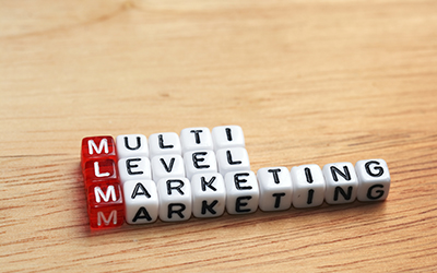 MLM Multi Level Marketing written on dices on wooden background